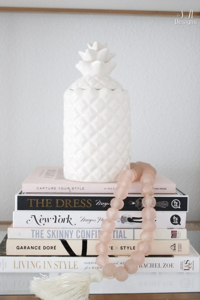 fashion books, fashion coffee table books, style books, blush pink sea glass beads, pineapple ceramic candle, ikea hack shelves, glam style office, decorating with books