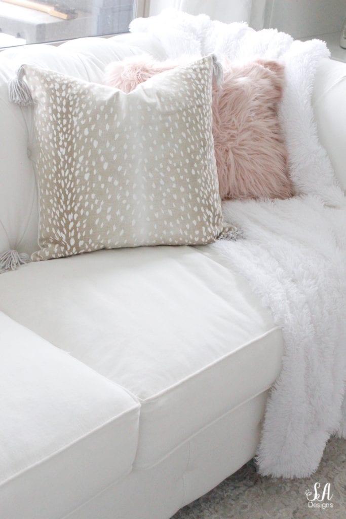 loveliest looks of fall tour, beige taupe fawn print pillow cover tassels, blush faux fur pillow, white tufted chesterfield sofa nailhead trim, white faux fur throw blanket