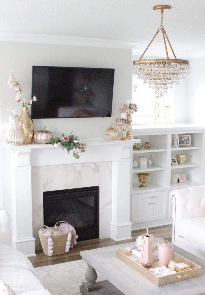 blush pink glass pumpkins, homegoods pumpkins, blush glam fall mantel decor, eucalyptus blush pink mauve roses swag, crystorama calypso chandelier, brass gold crystal chandelier, television over mantel mantle, tv above fireplace, mercury glass gold silver candle holders candle rings candle wreaths, fall glam candle rings, blush candle rings, white built-ins, white interiors, white hearth marble tile
