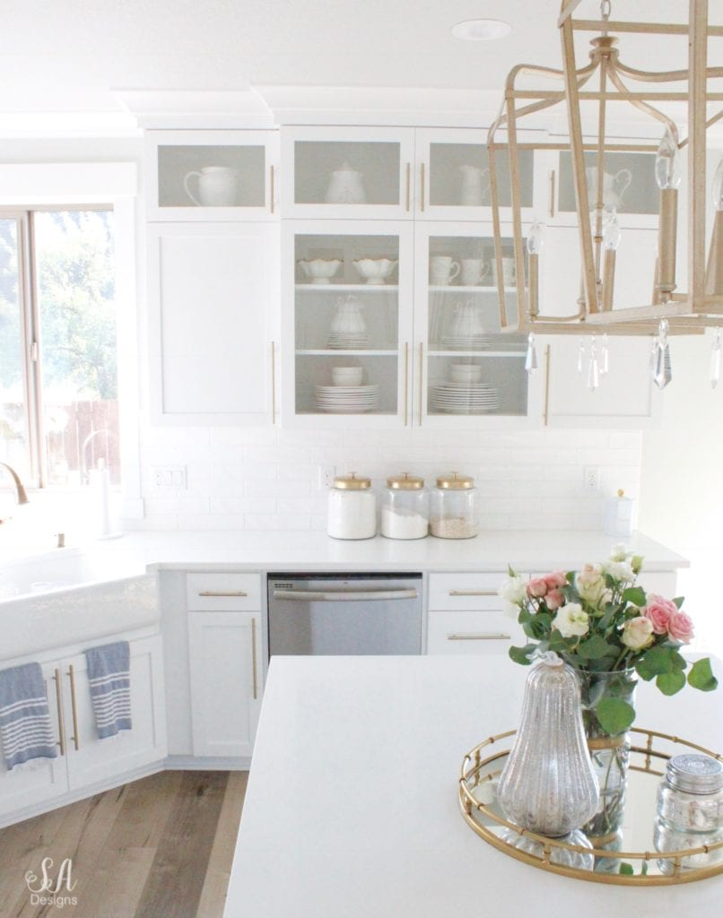 white kitchen design, shaker kitchen cabinets, kitchen island brass pendant lighting, white and gold, fall decor fall decorations, glam fall decor, elegant classy fall decor decorations, mercury glass pumpkins, fresh roses, brass mirrored tray, fall kitchen, styling a kitchen island